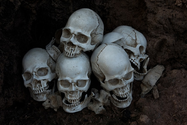 El cráneo humano y la pila de huesos sobre fondo negro, la noche de halloween