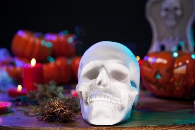 Cráneo humano sentado en una mesa de madera con calabaza aterradora celebrando halloween. velas de halloween.