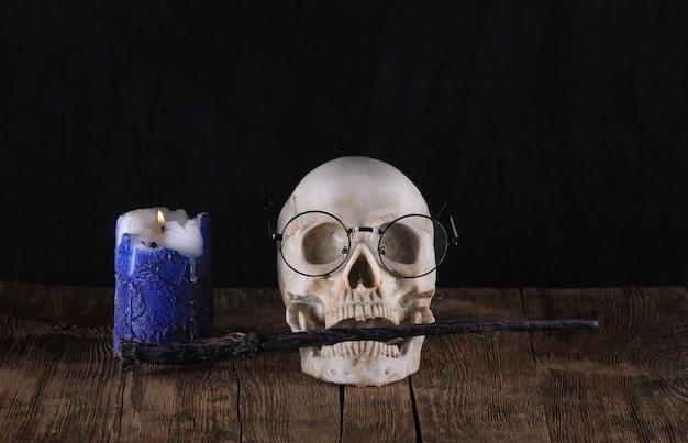 Cráneo humano y varita mágica sobre fondo negro