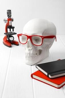 Cráneo humano de yeso en vasos rojos con blocs de notas, microscopio en la mesa de madera blanca