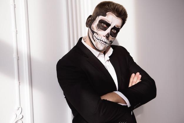 Cráneo maquillaje retrato de hombre joven. arte de cara de halloween