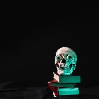 Cráneo de miedo con ojos de lujo acostado en la pila de libros