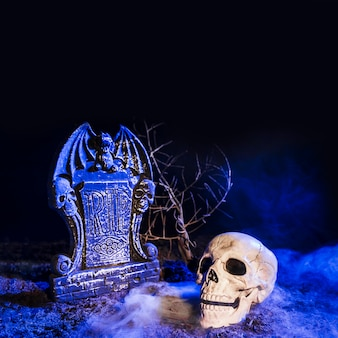 Cráneo sombrío cerca de lápida en el suelo