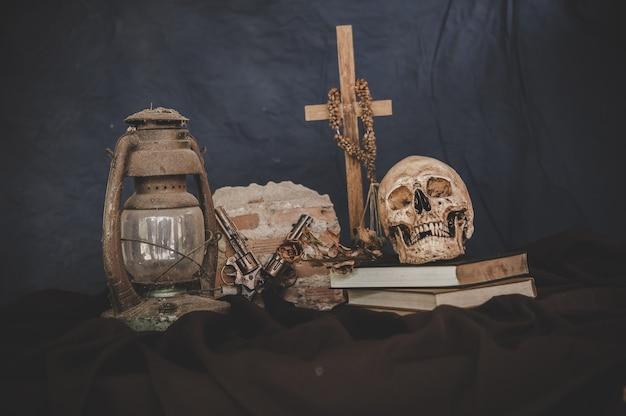 Cráneos en libros con viejas lámparas y pistolas cruzadas