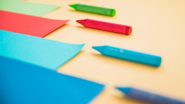 Crayón de cera color y papel de tarjeta dispuestos en una fila