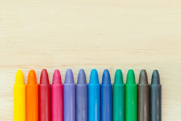 Crayon colores sobre fondo de madera con espacio de copia
