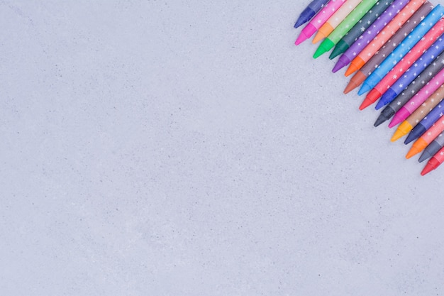 Crayones de colores aislados en superficie gris