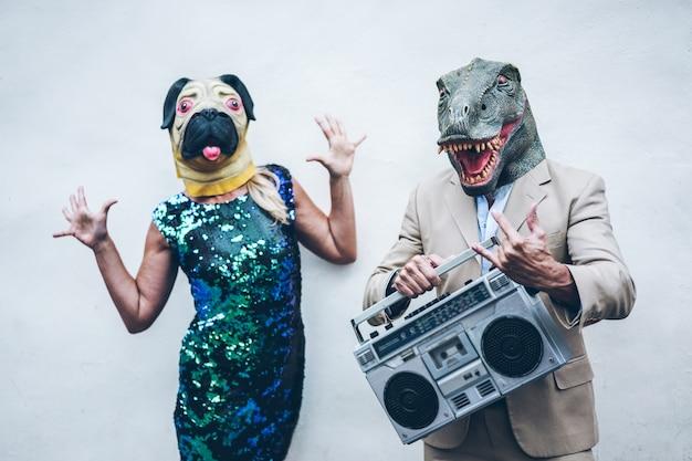 Crazy senior pareja bailando para la fiesta con t-rex y máscara de pollo: personas de moda que se divierten escuchando música con el estéreo boombox