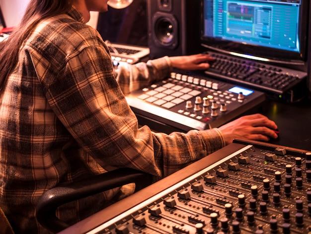 Creación de música electrónica en el estudio de casa con almohadillas, panel de sonido y teclas de la batería