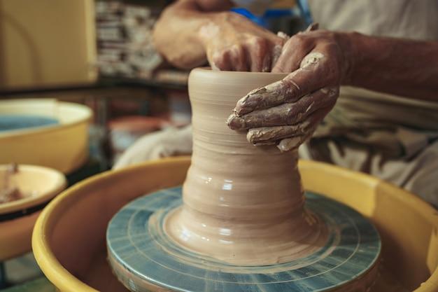 Creación de un primer plano de una jarra o jarrón de arcilla blanca. maestro olla. manos de hombre haciendo macro de jarra de arcilla. el escultor en el taller hace una jarra de primer plano de loza. torno de alfarero retorcido.