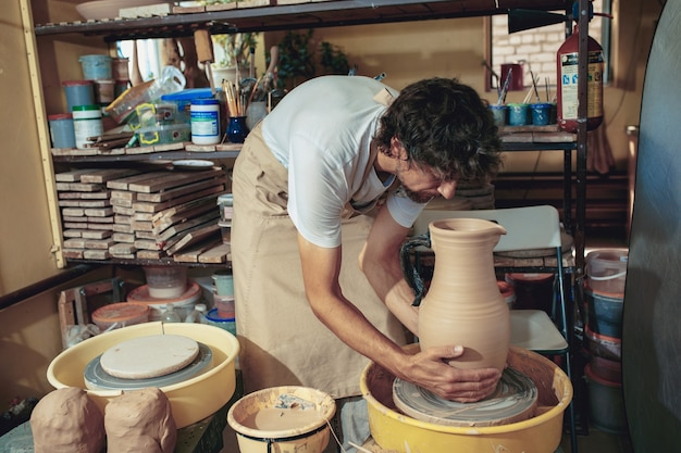 Creación de un primer plano de una jarra o jarrón de arcilla blanca. maestro olla.