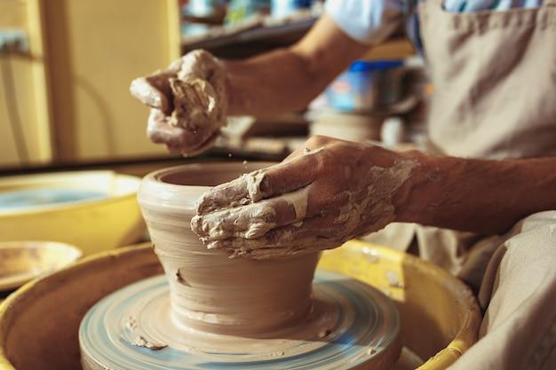 Creando un frasco o jarrón de arcilla blanca de cerca. maestro cántaro. manos de hombre haciendo macro jarra de arcilla.