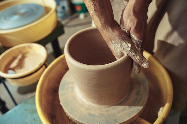Creando un frasco o jarrón de arcilla blanca de cerca. maestro cántaro.
