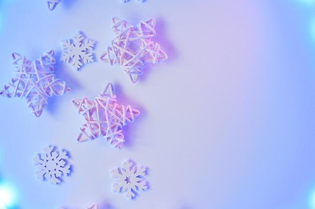 Creativa decoración de copos de nieve y estrellas blancas navideñas en neón púrpura