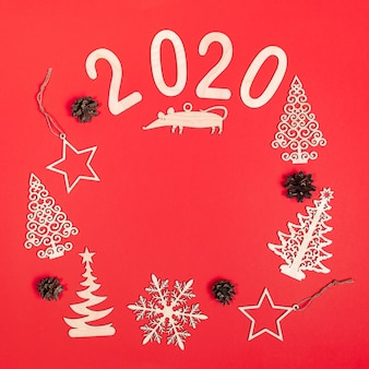 Creativa escena cuadrada de navidad sobre fondo rojo con decoraciones de madera diy, números 2020, ratas, conos y espacio de copia.