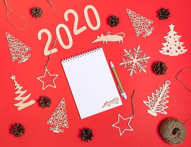 Creativa escena navideña sobre fondo rojo con decoraciones de madera de navidad