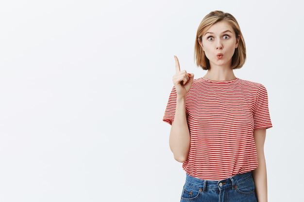 Creativa linda chica tiene una idea, levantando el dedo eureka gesto emocionado