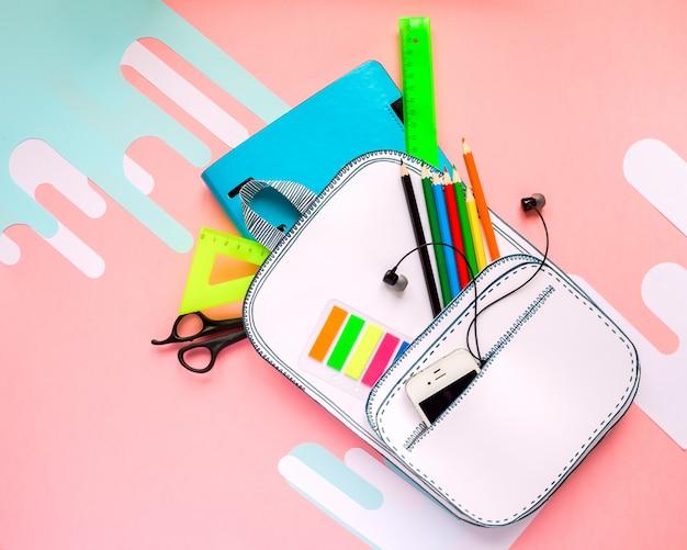 Creativa mochila escolar de papel con papelería escolar. de cerca.
