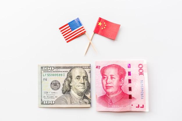 Creativa vista superior plana de la bandera de china y estados unidos y dinero en efectivo dólar estadounidense y billetes de yuan chinos