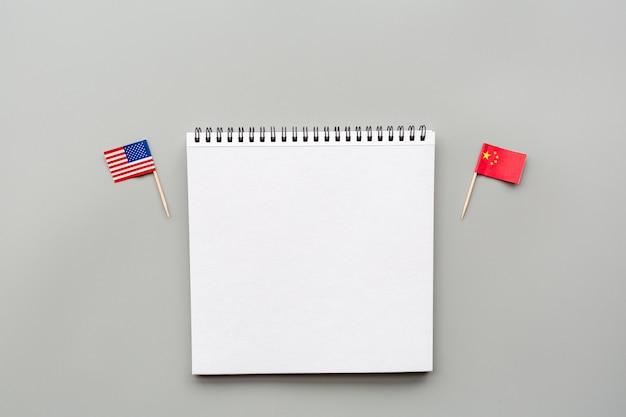Creativa vista superior plana de banderas de ee. uu. y china, maqueta y espacio de copia en gris