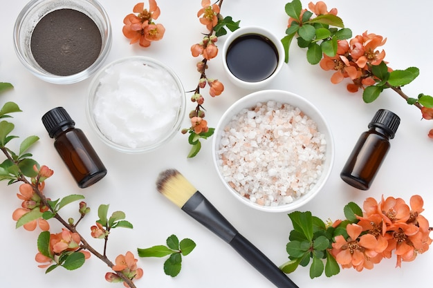 Creative flat lay with beauty, productos de spa para el cuidado del cuerpo, ramas de membrillo japonés.