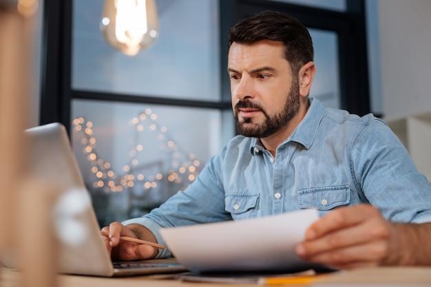 Creatividad e innovación. diseñador masculino inteligente creativo sosteniendo un dibujo y usando la computadora portátil mientras busca nuevas ideas