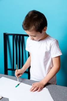 Creatividad infantil. niño pintar con pintura sobre fondo azul, vista superior