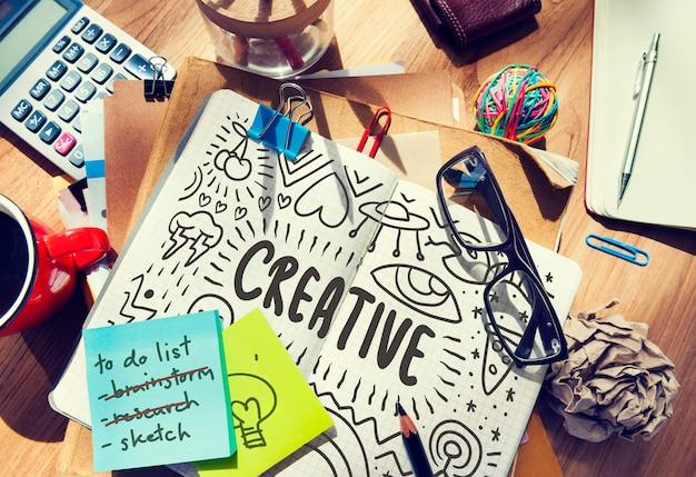 Creativo dibujado en un cuaderno sobre una mesa desordenada.
