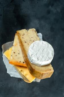 Creativo diferentes tipos de queso, por la que se sobre fondo oscuro con espacio de copia. camembert, queso con especias, queso holandés. gran cartel para tienda de quesos. fondo de alimentos enfoque suave