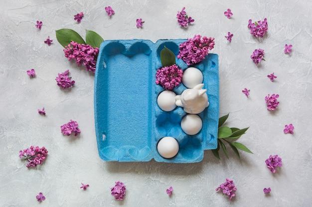 Creativo paquete de huevos con conejo y flores decorativas de color lila superficie clara