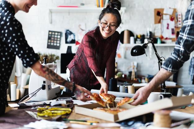 Creativos divirtiéndose, comiendo pizza.