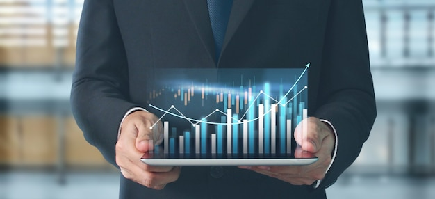 Crecimiento del gráfico del plan de negocios y aumento de los indicadores positivos del gráfico en su negocio, tableta en mano