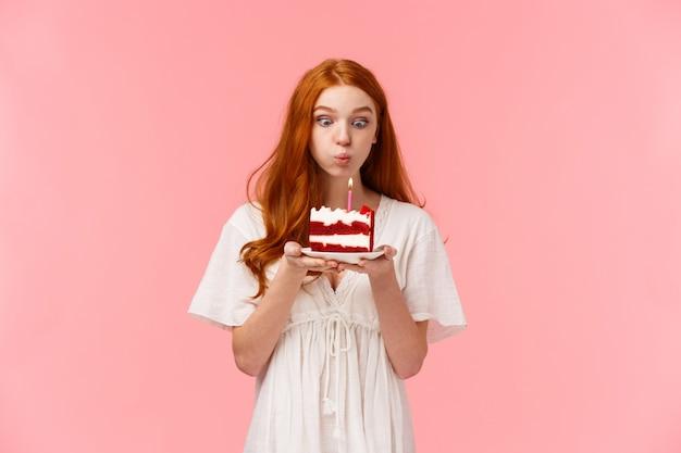 Cree en el milagro. linda y tonta chica pelirroja deseosa que pide un deseo en el cumpleaños, apagando la vela en el pastel de cumpleaños con expresión centrada, divirtiéndose, festejando y celebrando en el círculo familiar