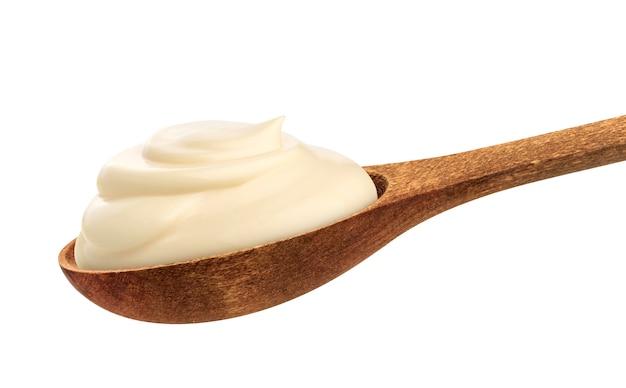 Crema agria en cuchara aislado en blanco