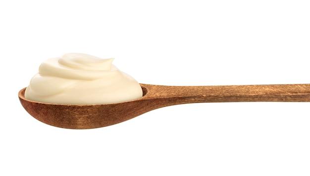 Crema agria en cuchara de madera aislada en blanco