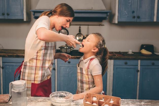 Crema batida batida. feliz familia amorosa están preparando panadería juntos. madre e hija hija están cocinando galletas y divirtiéndose en la cocina. envuelve la masa.