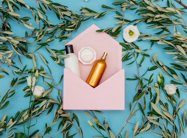 Crema y botella en sobre rosa con rama de olivo sobre fondo azul.