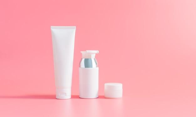 Crema de botellas blancas. paquete de etiqueta en blanco para cosmética en el fondo rosa