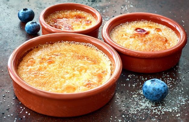 Crema brulee (crema brulee, crema quemada) en platos para hornear de terracota