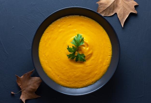 Crema de calabaza servida en un plato negro sobre un fondo oscuro con hojas de otoño