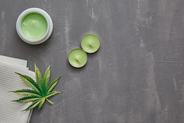 Crema de cáñamo de cannabis con hojas de marihuana y velas sobre una mesa de hormigón gris con espacio de copia. concepto de cosméticos tópicos de cannabis.
