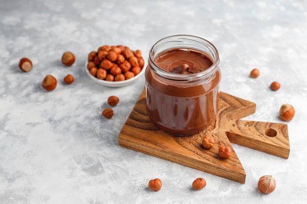 Crema de chocolate o turrón con avellanas en frasco de vidrio sobre hormigón, copyspace
