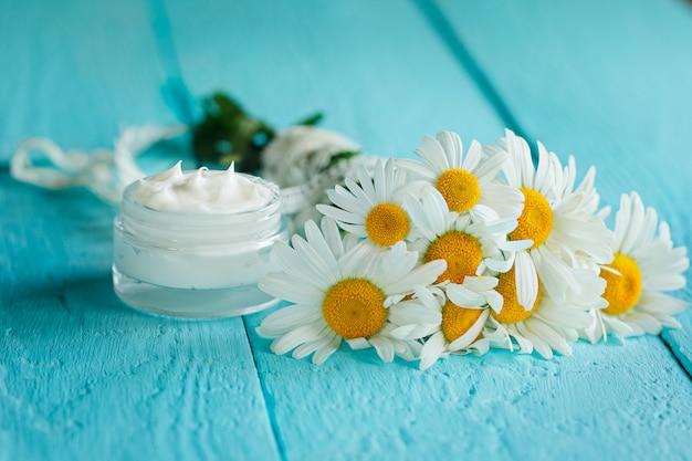 Crema cosmética con flor de manzanilla o cuerpo y cara en mesa de madera azul