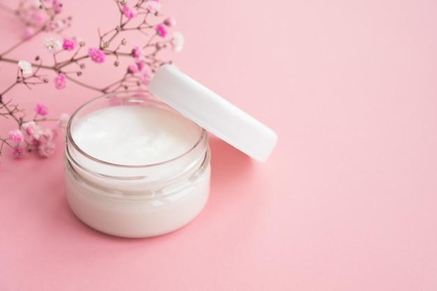 Crema cosmética en un frasco y flores sobre fondo rosa. cosmética natural, cuidado de la piel.