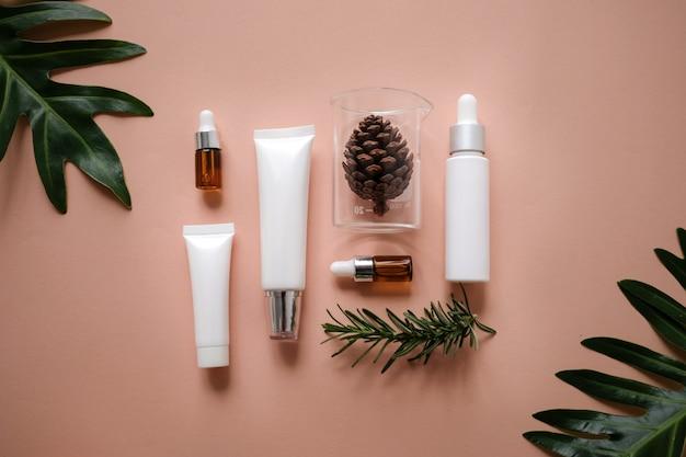 Crema cosmética natural, suero, cuidado de la piel en blanco frasco envasado con hojas.