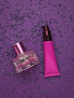 Crema cosmética y perfume sobre una superficie de globos púrpuras. kit de cuidado facial.