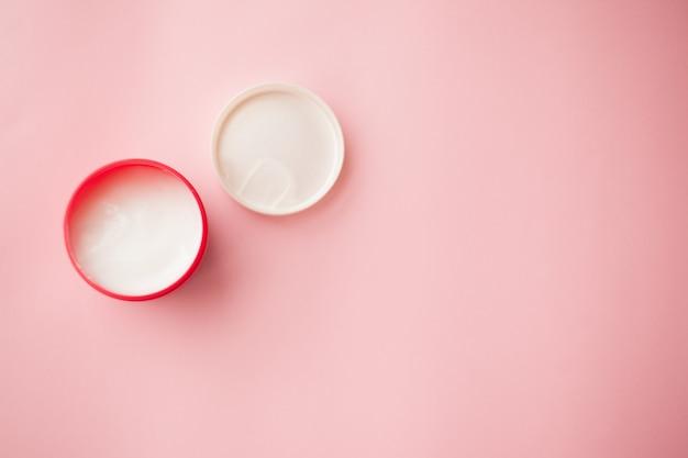Crema cosmética en un tarro rojo en un fondo rosado. protección de la piel.