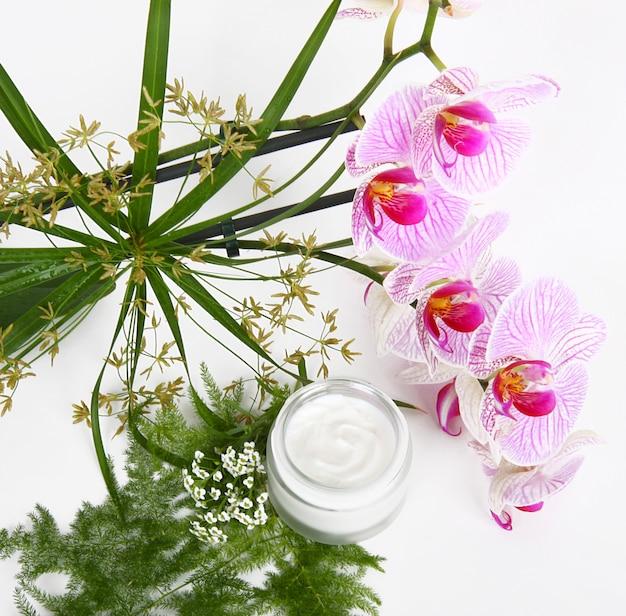 Crema facial con hierbas y orquídeas rosas.