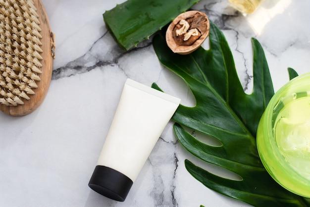Crema facial sobre fondo de hoja de palma, ingredientes naturales y fondo de mármol.