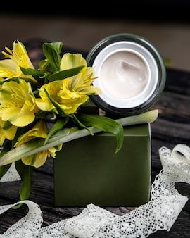 Crema con flores sobre la mesa